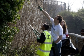 Volunteers from Deloitte help a student from Eastlea Community School cut back vegetation at Three Mills Island Bromley-by-Bow, London
